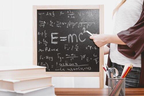 Math tutor showing formulas on chalkboard.